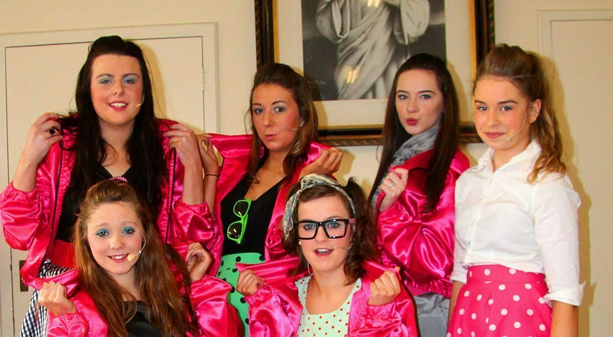 Sandy alongside The Pink Ladies - the group of club-jacketed, gum-chewing girls group that hang around the T-Birds